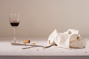 Wine glass cutlery dish cloth on messy tableの写真素材 [FYI03639150]