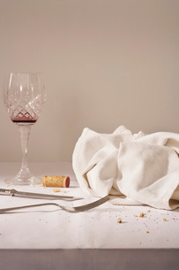 Wine glass cutlery dish cloth on messy tableの写真素材 [FYI03639151]