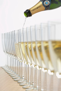 Bottle of champagne filling row of glasses selective focusの写真素材 [FYI03639184]