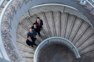 Four business associates standing on spiral staircase portraの写真素材 [FYI03639357]