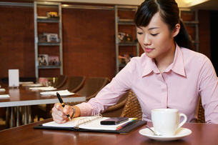 Business woman writing in diary sitting in cafeの写真素材 [FYI03639360]
