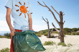 Boy (10-12) holding plastic bag on sand dune mid sectionの写真素材 [FYI03639374]