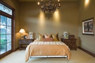 Chandelier hangs over bed in Palm Springs homeの写真素材 [FYI03639899]