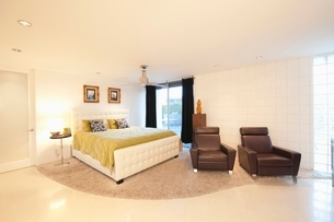 Partly carpeted bedroom with matching leather armchairsの写真素材 [FYI03640014]