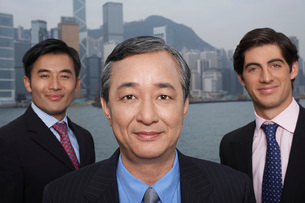 Portrait of three business men office buildings in backgrounの写真素材 [FYI03640096]