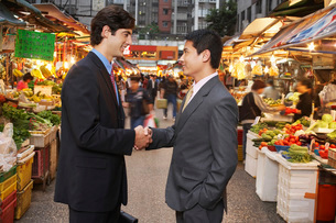 Two business men shaking hands at street marketの写真素材 [FYI03640101]