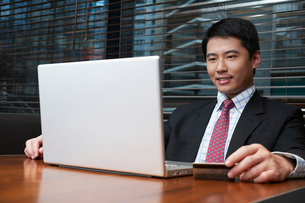 Business man using laptop in cafeの写真素材 [FYI03640104]
