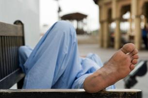 Dubai UAE man taking rest on park bench along boardwalk in Bの写真素材 [FYI03640351]