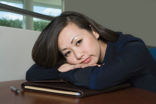 Bored Asian Businesswoman with Head on Deskの写真素材 [FYI03640464]