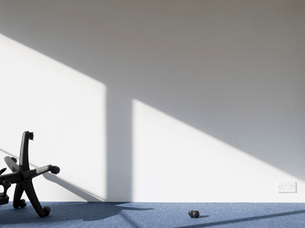 Broken office chair casting shadow on wallの写真素材 [FYI03640565]