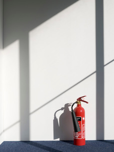 Fire extinguisher casting shadow on wallの写真素材 [FYI03640579]