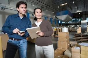 Man and woman in distribution warehouseの写真素材 [FYI03640602]