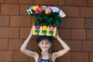 Portrait of little girl carrying artificial flowers in woodeの写真素材 [FYI03640697]