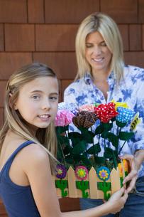 Portrait of a little girl handing over artificial flowers inの写真素材 [FYI03640699]