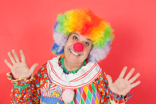 Portrait of funny clown with arms raised against colored bacの写真素材 [FYI03640719]