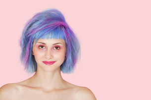Portrait of beautiful young woman with dyed hair against pinの写真素材 [FYI03640723]
