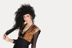 Portrait of young Goth woman with teased hair over gray backの写真素材 [FYI03640730]