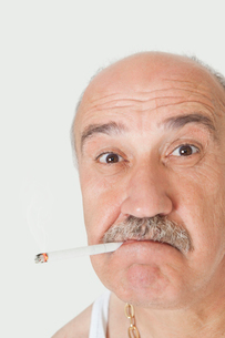 Portrait of senior man with cigarette in mouth over gray bacの写真素材 [FYI03640732]