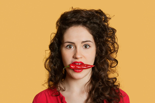 Portrait of a young woman with red chili pepper in mouth oveの写真素材 [FYI03640764]