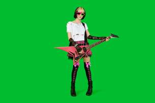 Punk woman with guitar over green colored backgroundの写真素材 [FYI03640790]