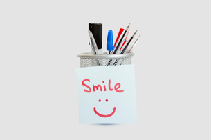 Close-up of adhesive notepaper with smiley face stuck on penの写真素材 [FYI03640829]