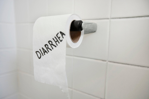 Close-up of toilet paper roll with diarrhea written in bathrの写真素材 [FYI03640841]
