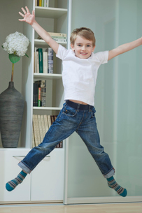 Portrait of a boy in casuals jumping in mid-air at homeの写真素材 [FYI03640868]