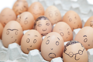 Various facial expressions painted on brown eggs in egg cartの写真素材 [FYI03640869]