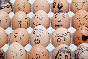 Funny faces on painted on brown eggs arranged in cartonの写真素材 [FYI03640871]