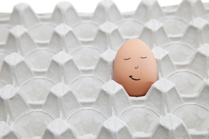 Anthropomorphic face drawn on brown egg in empty cartonの写真素材 [FYI03640875]