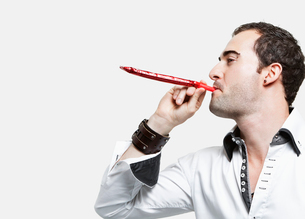 Young man blowing party blower against gray backgroundの写真素材 [FYI03640877]