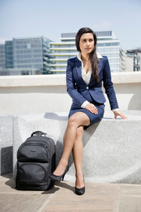 Young Indian businesswoman with luggage sitting outdoorsの写真素材 [FYI03640881]