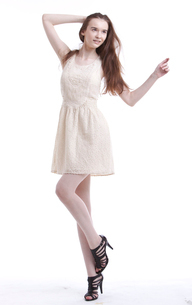 Beautiful young woman in dress with hand in her hair lookingの写真素材 [FYI03640894]