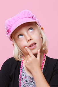 Thoughtful young girl wearing cap with finger on chin over pの写真素材 [FYI03640925]