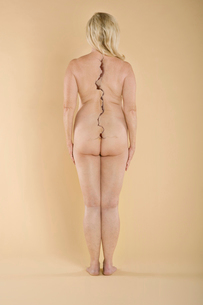 Rear view of a nude woman with a crack on spine standing oveの写真素材 [FYI03640931]