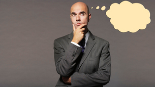 Bald businessman thinking with speech bubble over gray backgの写真素材 [FYI03640940]