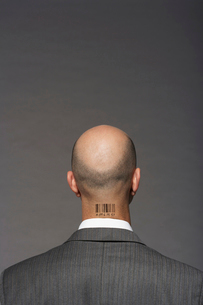Bald headed businessman with barcode on his neck over gray bの写真素材 [FYI03640941]