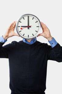 Young man covering his face with clock standing against whitの写真素材 [FYI03640948]