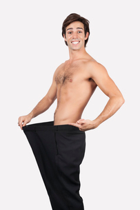 Portrait of happy young man wearing oversized pants againstの写真素材 [FYI03640955]