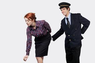Portrait of young pilot touching flight attendant inappropriの写真素材 [FYI03640956]