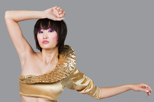 Portrait of young woman in golden costume over gray backgrouの写真素材 [FYI03640959]