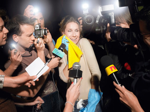 Woman with cleaning equipment surrounded by paparazziの写真素材 [FYI03640992]