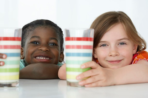 Two girls (5-6) leaning on table holding colourful glasses pの写真素材 [FYI03640993]