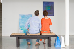 Couple contemplating paintings in galleryの写真素材 [FYI03641032]