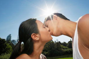 Couple kissing in park in bright sunlightの写真素材 [FYI03641042]