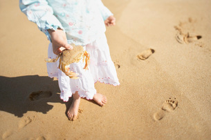 Girl holding crab in hand standing on beach low sectionの写真素材 [FYI03641047]
