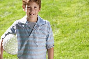 Boy holding ball in park portraitの写真素材 [FYI03641067]