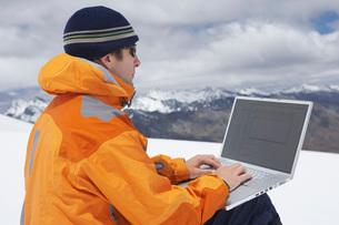 Hiker using laptop on snowy mountain peakの写真素材 [FYI03641068]