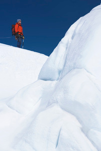 Mountain climber hiking past ice formationの写真素材 [FYI03641072]