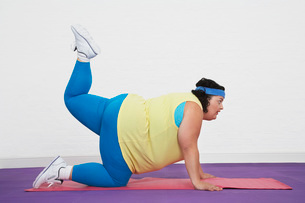 Overweight Woman on floor doing aerobic stretchesの写真素材 [FYI03641172]